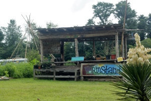 Front of the farmstand where potted plants, produce and handmade items are displayed